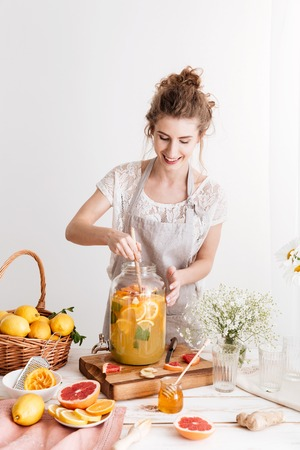 Image of amazing concentrated woman standing indoors cooking citrus beverage. Looking aside.