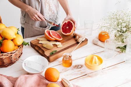 Cropped picture of young woman standing indoors near table with a lot of citruses and cut the grapefruit. Stock Photo
