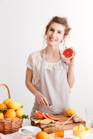 Young happy woman standing indoors near table with a lot of citruses and cut the grapefruit. Looking at camera. Stock Photo