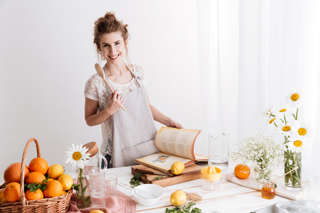 Picture of amazing young woman standing indoors near table with a lot of citruses holding cooking book. Looking camera.