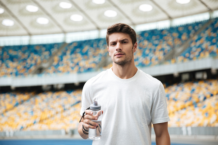 Young male athlete holding bottle of water while standing at the racetrack