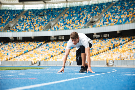 Young male sprinter about to start a race at the stadium