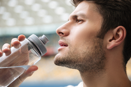 Close up profile portrait of a handsome man drinking water from a bottle at the stadium Stock Photo