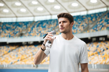 Tired sportsman holding water bottle while standing at the racetrack Stock Photo
