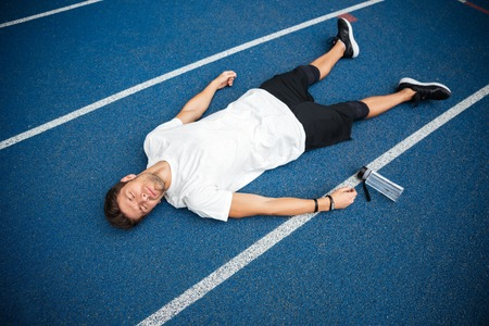 Tired young sportsman lying on a racetrack with bottle of water at the stadium