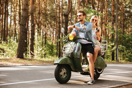 Image of young handsome man on scooter with girlfriend holding camera outdoors. Looking aside.
