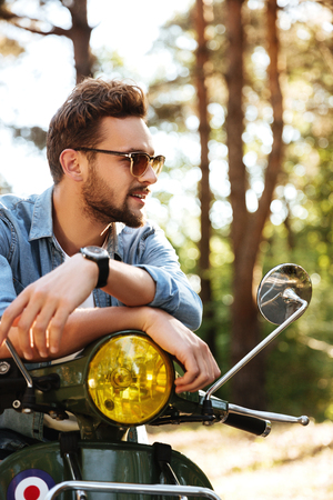 Image of concentrated young bearded man sitting on scooter outdoors. Looking aside. Stock Photo