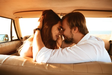 Close up of a beautiful young couple in love kissing while sitting together inside a retro car on a front seat