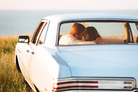 Back view of a smiling attractive couple in love sitting and kissing on a back seat of a car Reklamní fotografie - 84178726