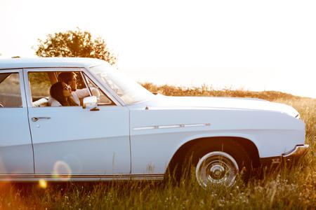Jong koppel zitten in retro auto geparkeerd buitenshuis Stockfoto