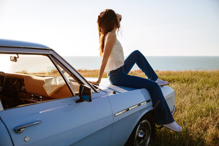 Young attractive woman relaxing while sitting on a car outdoors and looking at the landscape 免版税图像 - 84178694