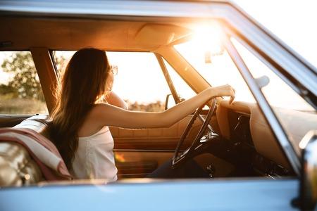 복고풍 자동차 안에 앉아서 스티어링 휠에 손을 잡고 젊은 여자의 측면보기 스톡 콘텐츠