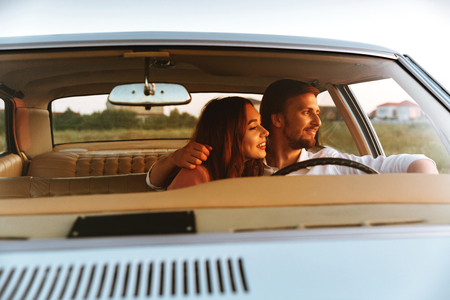 Smiling young couple hugging while sitting together inside a car and looking away. front window view