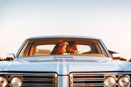 Beautiful young couple kissing while sitting together in an old retro car. Front window view