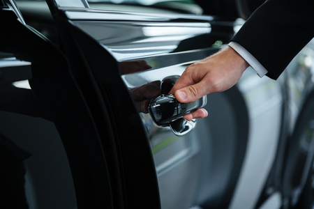 Close up of a male hand closing a car door at the dealership Banco de Imagens
