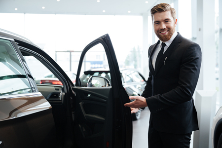 Happy smiling male dealer inviting customers to sit in a new car