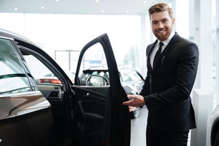 heureux sourire acheteur homme attente des clients à asseoir dans une nouvelle voiture Banque d'images