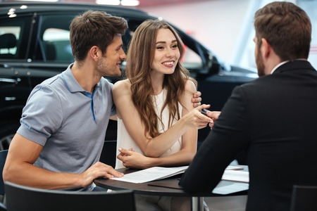 Confident young salesman explaining all the new car features to the young attractive owners Imagens