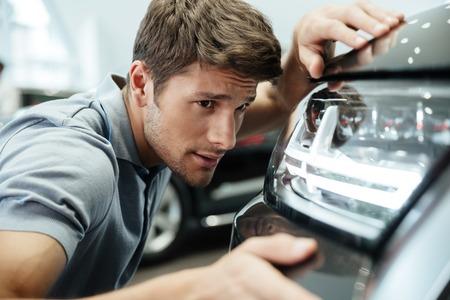 jeune client mâle examinant et en regardant soigneusement à une nouvelle voiture à un concessionnaire