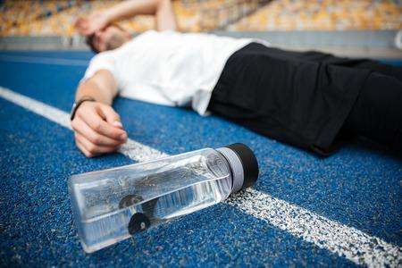 スタジアムで水のボトルを競馬場に横たわって疲れて若いスポーツマン
