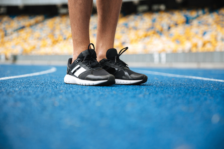 racetrack: Close up of a male legs in sneakers standing at the racetrack