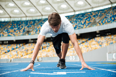 Confident male athlete standing in starting position ready for running at the stadium
