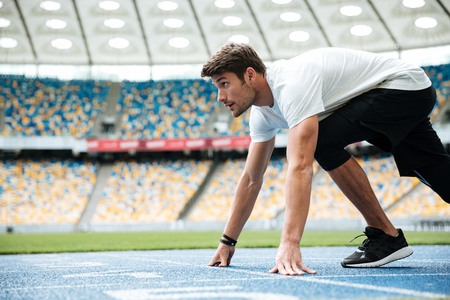 Side view of a male runner ready for sports exercise on a racetrack at the stadium