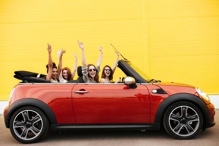 屋外の車に座って幸せの感情的な 4 人の若い女性の友人のイメージ。カメラを探しています。 写真素材