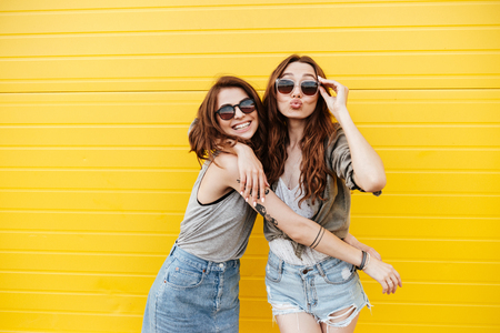 Image of two young happy women friends standing over yellow wall. Looking at camera blowing kisses. Stockfoto