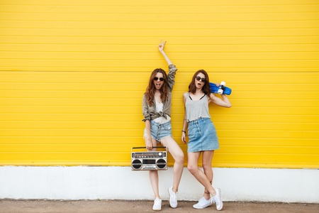 Image of two young happy women friends standing over yellow wall. Looking at camera holding boombox and skateboard.
