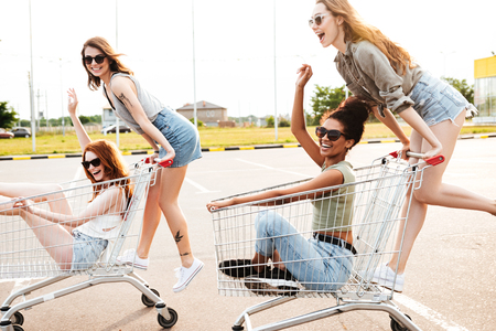 Picture of young amazing women friends have fun with shopping trolleys.
