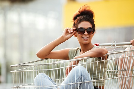 Smiling young african girl in sunglasses sitting inside a shopping trolley outdoors