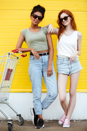 Image of two young happy ladies friends standing over yellow wall. Looking at camera. Stock Photo