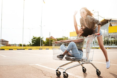 Image of young happy women friends have fun with shopping trolleys. Stock Photo