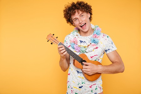 Attractive young man in summer clothes playing ukulele and singing isolated over yellow background Stock Photo