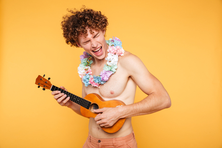 Attractive shirtless man in summer clothes playing ukulele and singing isolated over yellow background Stock Photo