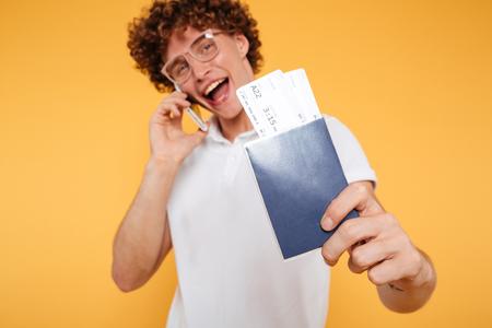 携帯電話で話していると、黄色の背景に分離された航空券とパスポートを見せて幸せな若い男の肖像 写真素材