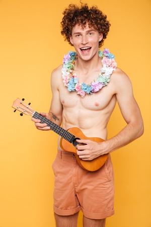 Young shirtless guy holding ukulele and looking at camera isolated over yellow background