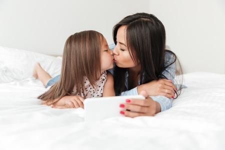 Foto della giovane donna stupefacente con la piccola figlia a casa all'interno facendo uso del telefono cellulare e baciare. Archivio Fotografico - 84527629