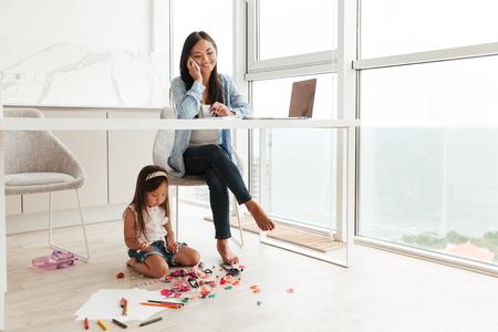 Joven asiática hablando por un teléfono móvil y trabajando en la computadora portátil mientras su pequeña hija jugando en un piso en casa