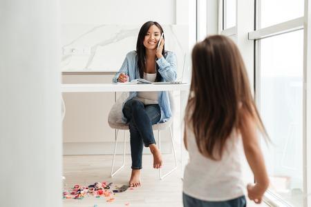 Mujer asiática sonriente hablando por un teléfono móvil y trabajando en la computadora portátil mientras su pequeña hija jugando en casa Foto de archivo - 84527649