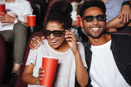 Attractive afro american couple watching 3D movie and laughing while sitting in a movie theater Фото со стока