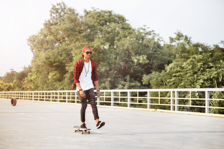 Picture of young attractive dark skinned guy wearing sunglasses and cap skateboarding. Against the nature background. Stock Photo