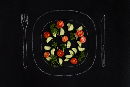Fresh summer salad on a hand drawn plate with fork and knife over black background Фото со стока - 84664977
