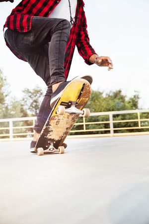 Photo of young dark skinned guy skateboarding. Against the nature background. Фото со стока