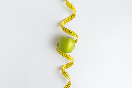흰색 배경에 절연 테이프를 측정 함께 신선한 녹색 사과