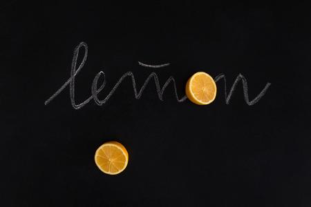Freshly cut orange fruit with the inscription over black background Zdjęcie Seryjne