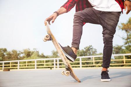 젊은 어두운 피부가 남자 스케이트 보드 자른 된. 자연 배경. 스톡 콘텐츠