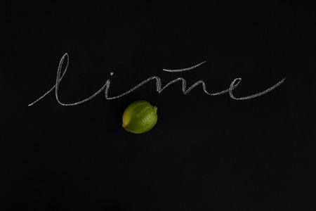 Rijpe verse limoen met de inscriptie op zwarte achtergrond Stockfoto