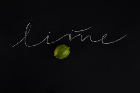 Ripe fresh lime with the inscription over black background